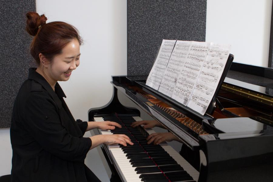 A faculty of music student plays the piano.