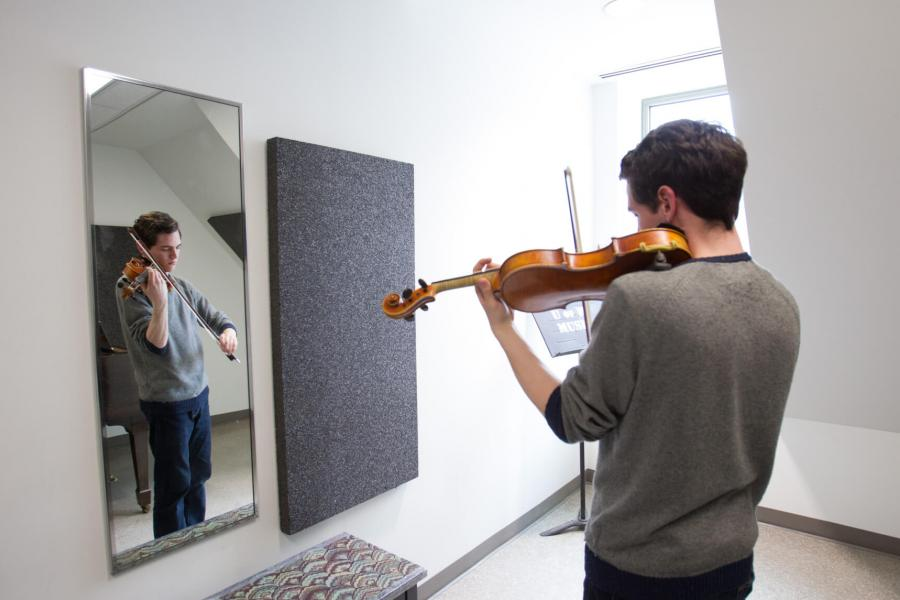 A student practices the violin in a practice room.