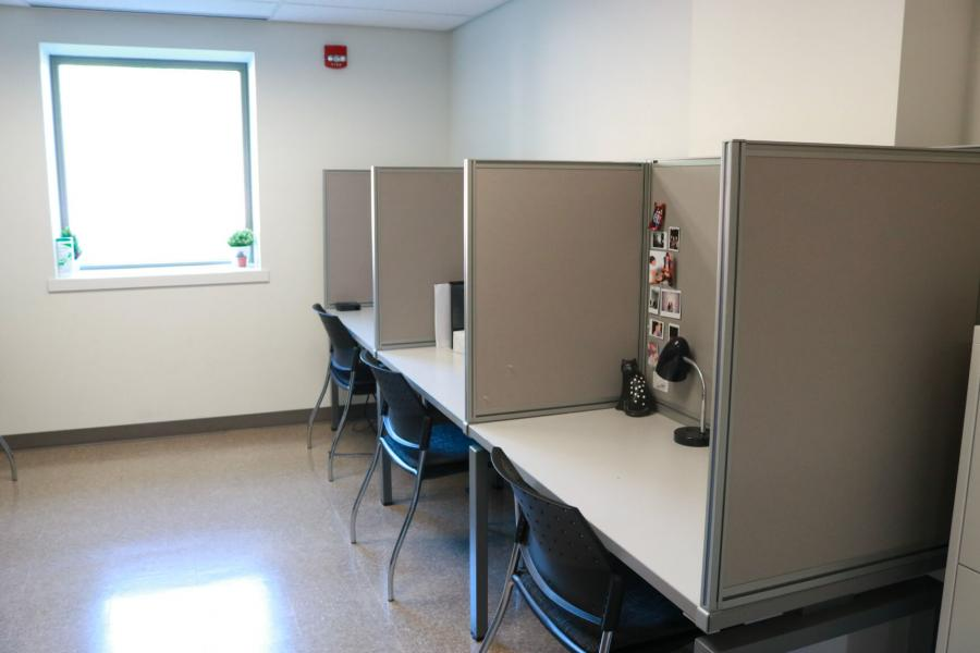 A brightly lit room with a window, and a long table along a wall partitioned off to created individual student office spaces decorated with photos and lamps.