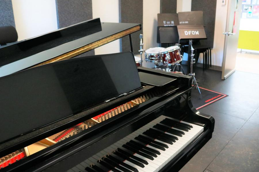 An interior of a jazz ensemble practice room with a piano and full drum kit and acoustic panelling lining the walls.