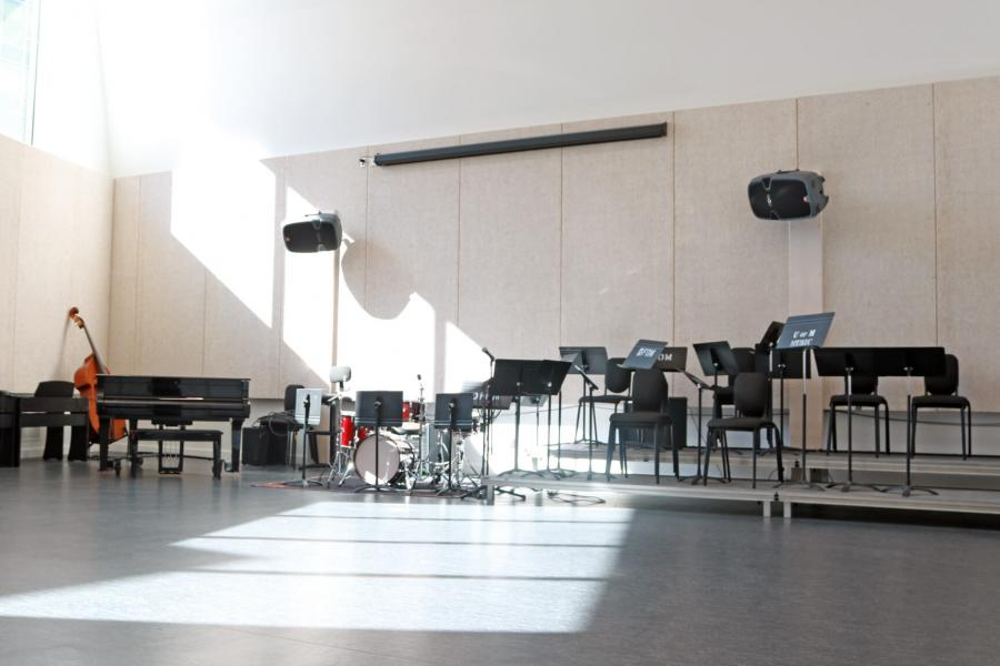 A spacious room with high ceilings and lots of natural light from windows various music instruments and equipment are lined up along a wall with a stage and large speakers mounted to the wall.