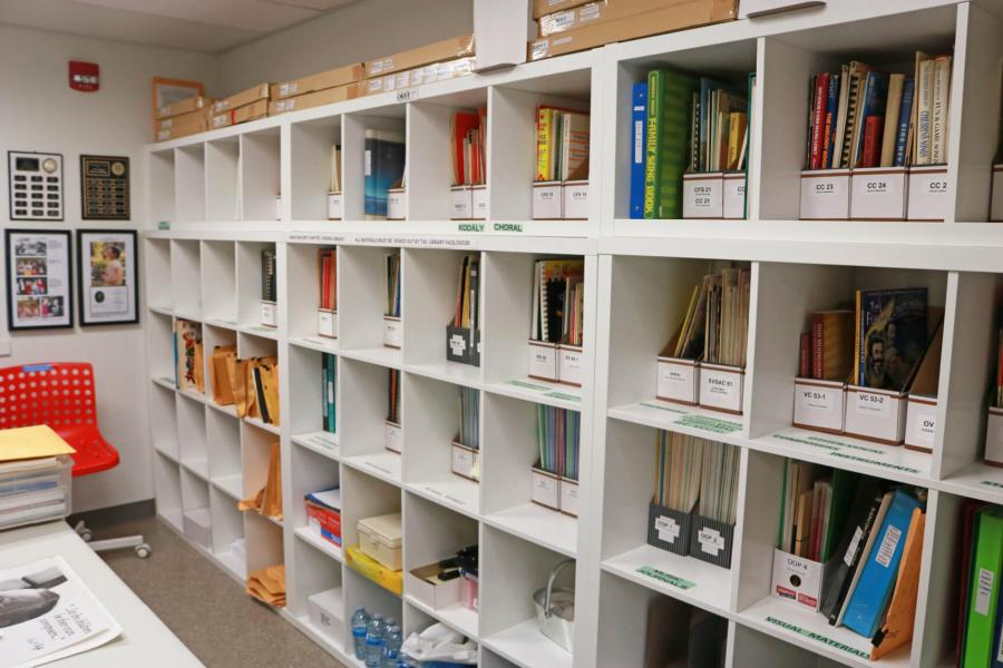 A portion of the interior of a room with a wall lined with shelving holding various pedagogy literature and materials.