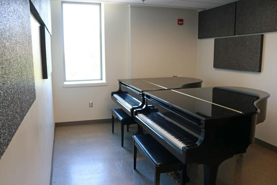 Inside a piano practice room with a tall narrow window and two pianos placed side by side.