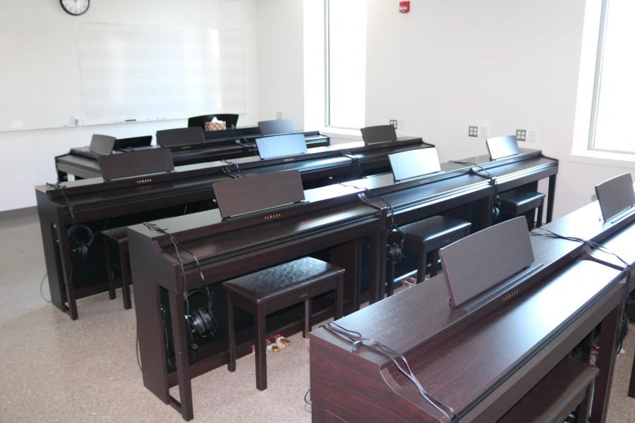 A room with a wall lined with tall narrow windows and another with a large white board. Multiple rows of three Yamaha keyboards fill the space.