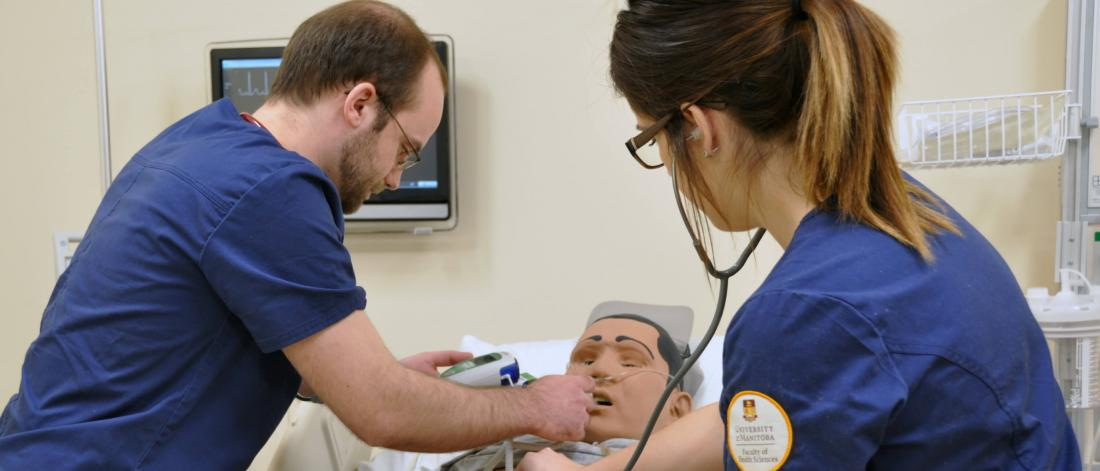 Two nursing students work in a robotic patient in the Sim Lab.