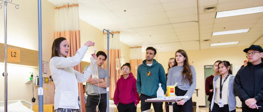Nursing students stand and watch an IV demonstration.
