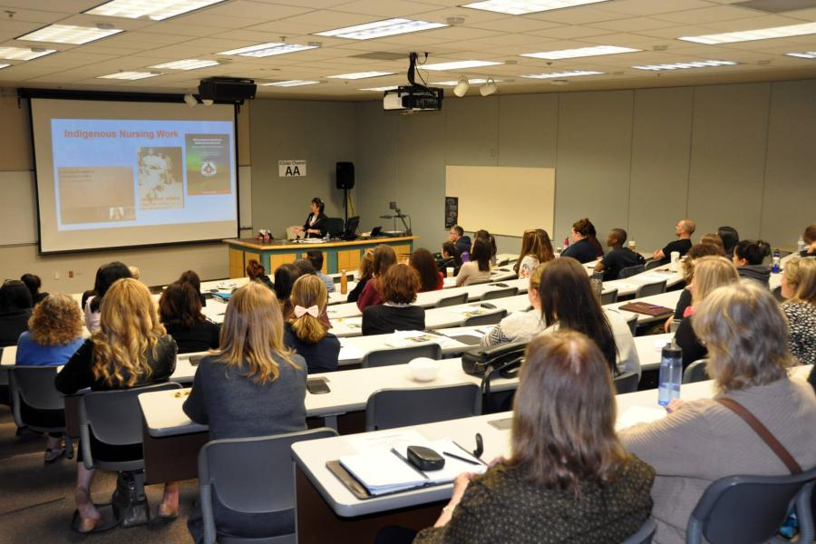 A classroom of Master of Nursing program students watch a presentation on a projector screen.