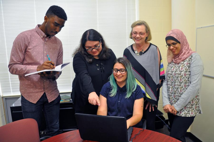 Four doctoral nursing students stand behind another who is seated at a table in front of a laptop.