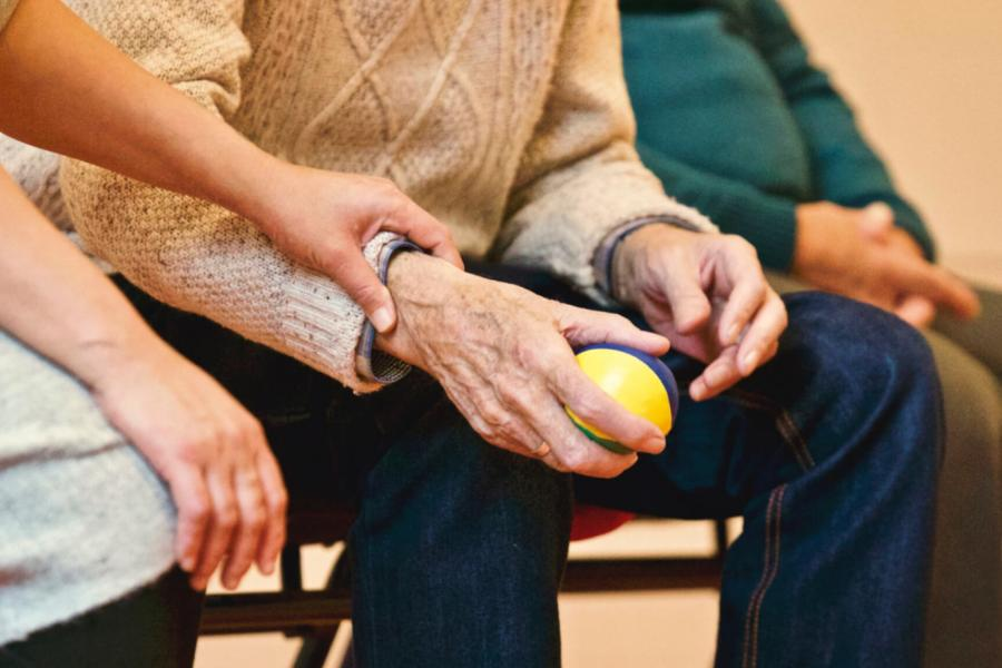 A woman gently holds the wrist of an elderly patient who is seated and holding a ball.