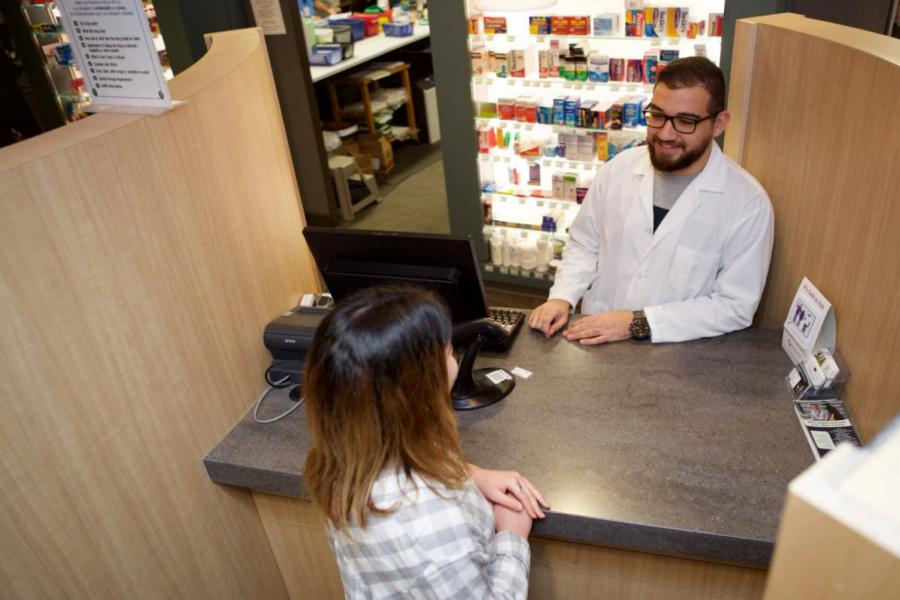 A Pharmacist talks with a customer from behind the checkout counter.