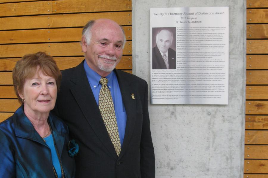 A smiling Dr. Wayne K. Anderson and his wife Lorraine stand together beside his Pharmacy Alumni of Distinction Award.