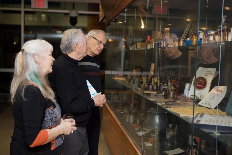 Three pharmacy alumni gather around a display case to take a look at the items inside.