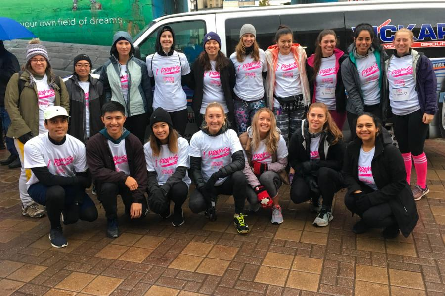 A group of pharmacy students huddle together for a photo wearing the same team tshirts for Canadian Cancer Society's Run for a Cure.