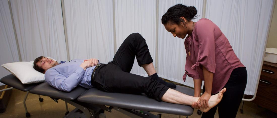 A patient lying down has their foot attended to my a physical therapist.