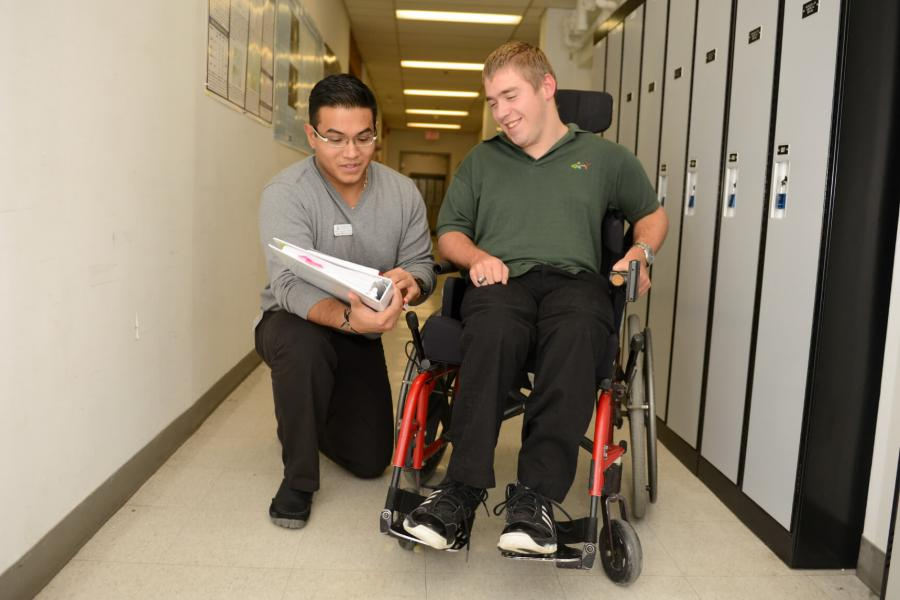 An occupational therapist kneels down in a hallway lined with lockers to show something to a patient in a wheelchair.