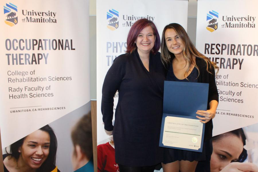 Occupational therapy student Andreea Alexandrescu stands holding her Future Scholar award.