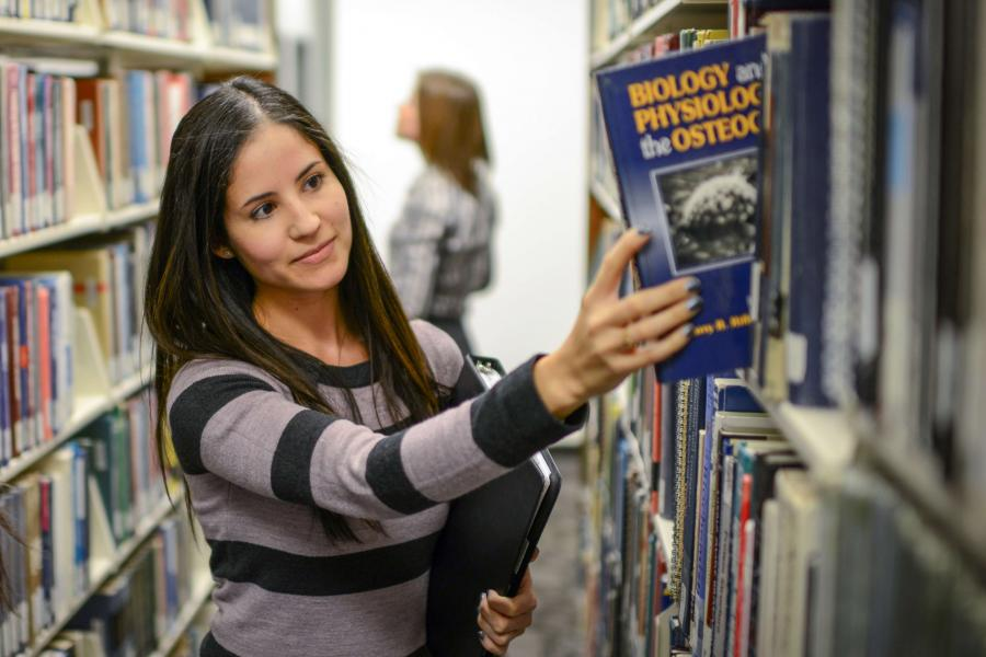 Student chooses a book from the library shelves