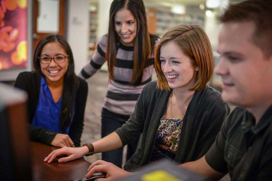 Group of students gathers around a computer monitor