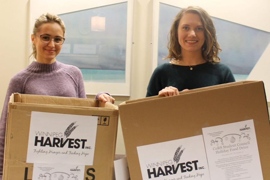 Students donating boxes of groceries to Winnipeg Harvest