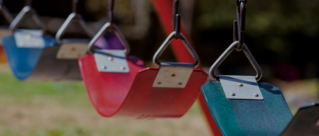 plastic swing seats in a playground, without children in them, different coloured seats