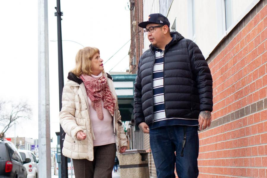 2019 Undergraduate Research award recipient Henry McKay walks down a Winnipeg street with his supervisor.