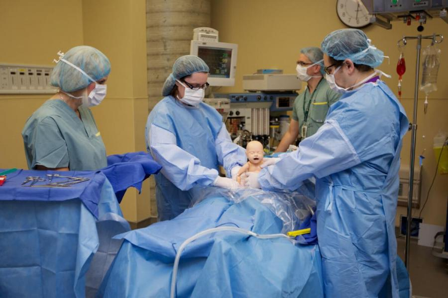 Students in scrubs at an operating table handling an infant mannequin.