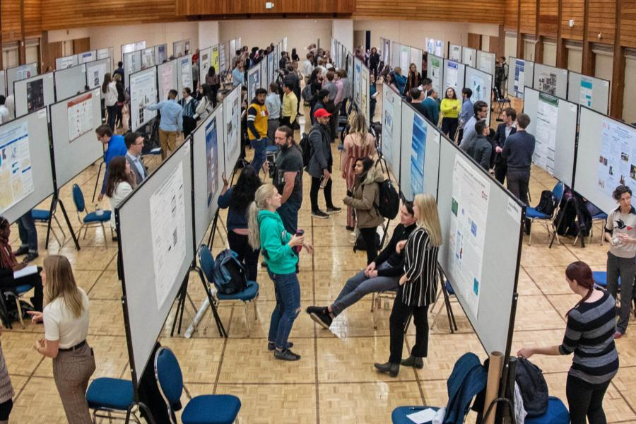 A room filled with undergraduate students standing beside their research posters while a crowd of attendees moves through the room and views everyones work.
