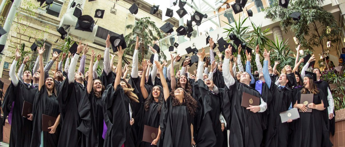 University of Manitoba students celebrate their graduation by tossing their mortarboard caps in the air together.
