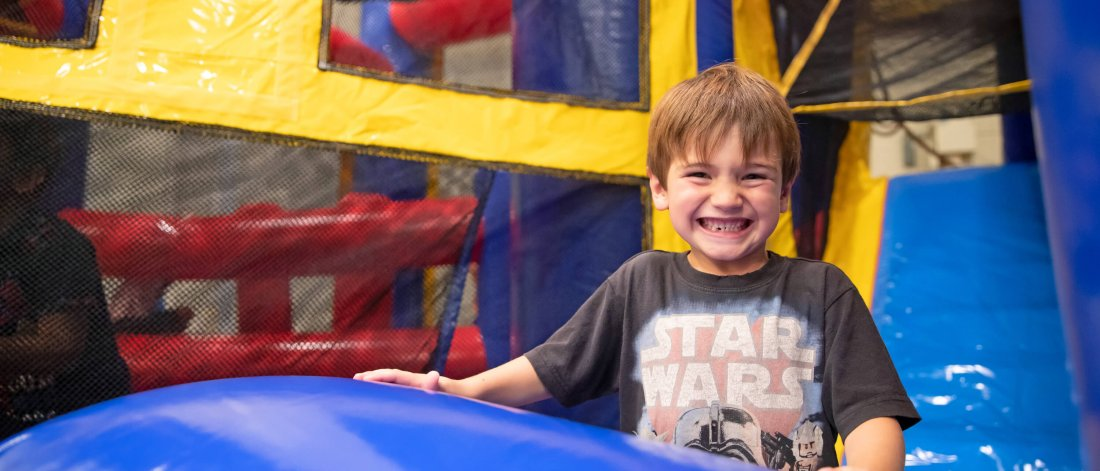 A smiling Mini U child playing in a bouncy castle.