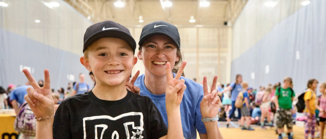 A Mini U leader and child smile at the camera making peace signs in a busy gymnasium.