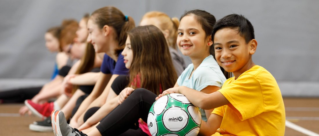 A group of children sit on the floor in a row together in a gymnasium, a young boy at the front holds a soccer ball.