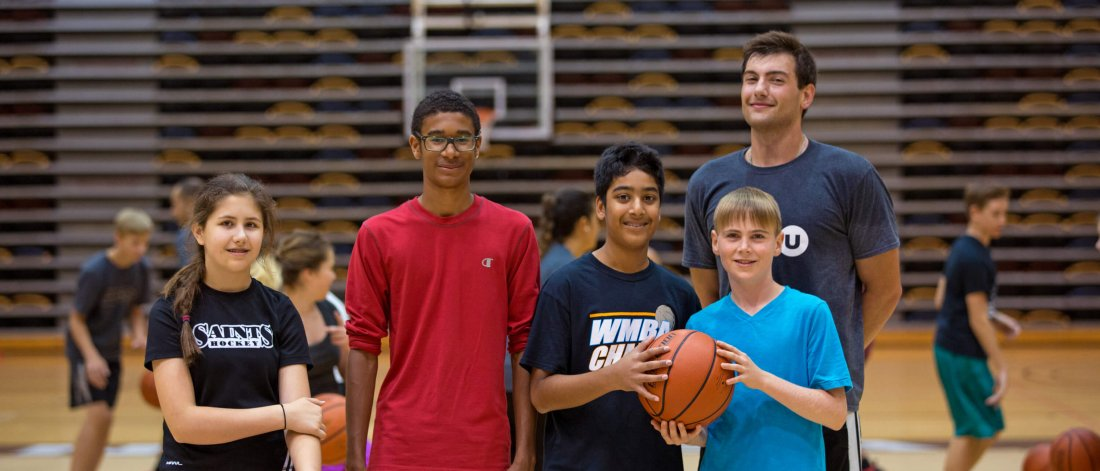 A group of young basketballers poses in the gym with their Mini U leader.