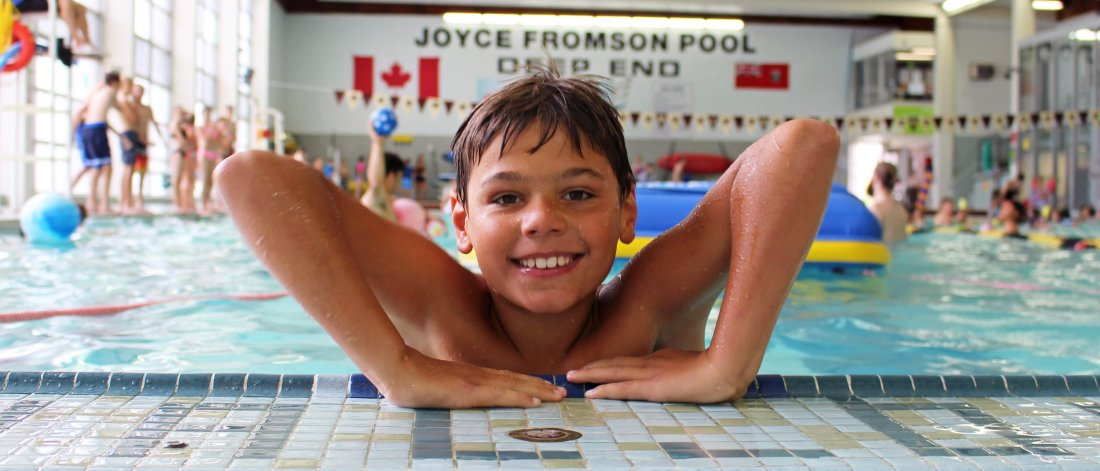 A young swimmer gets set to hoist himself out of the shallow end of the University pool.