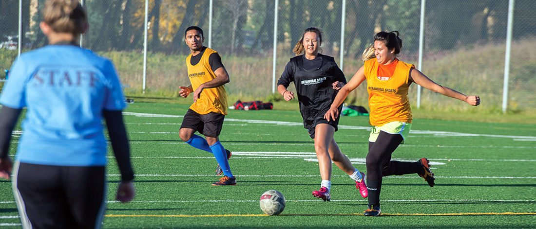 Opposing team members run for the ball during an outdoor intramural soccer game.