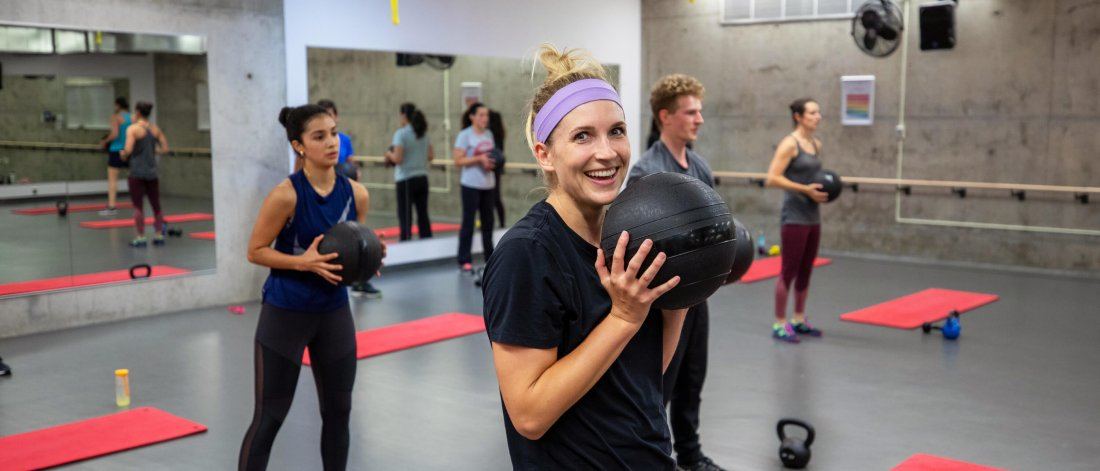 Several people in a group fitness class stand while holding medicine balls to their chests.