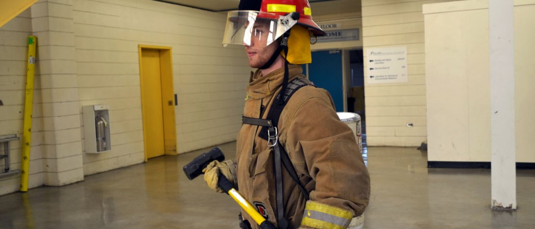 A fireman walks across a room in full gear carrying an axe.