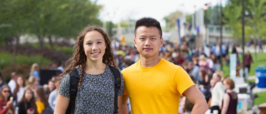 Two University of Manitoba students stand side by side outdoors at an orientation event.