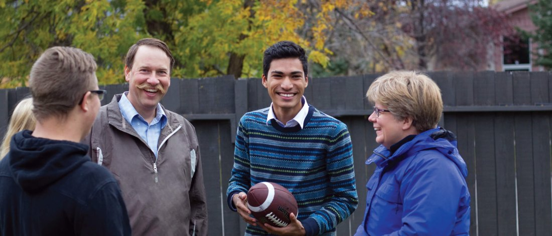 An international student stands in a backyard with his homestay host family.