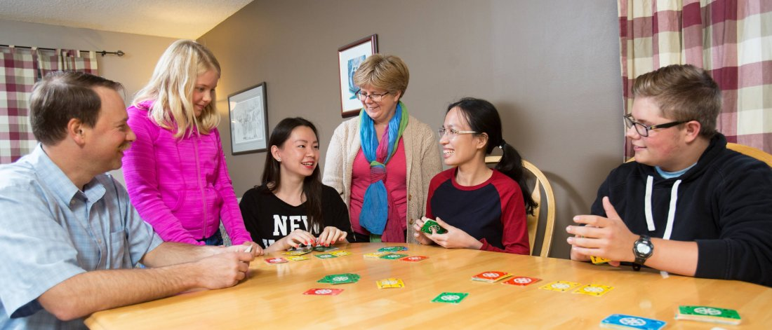 A homestay host family and student play a card game together.