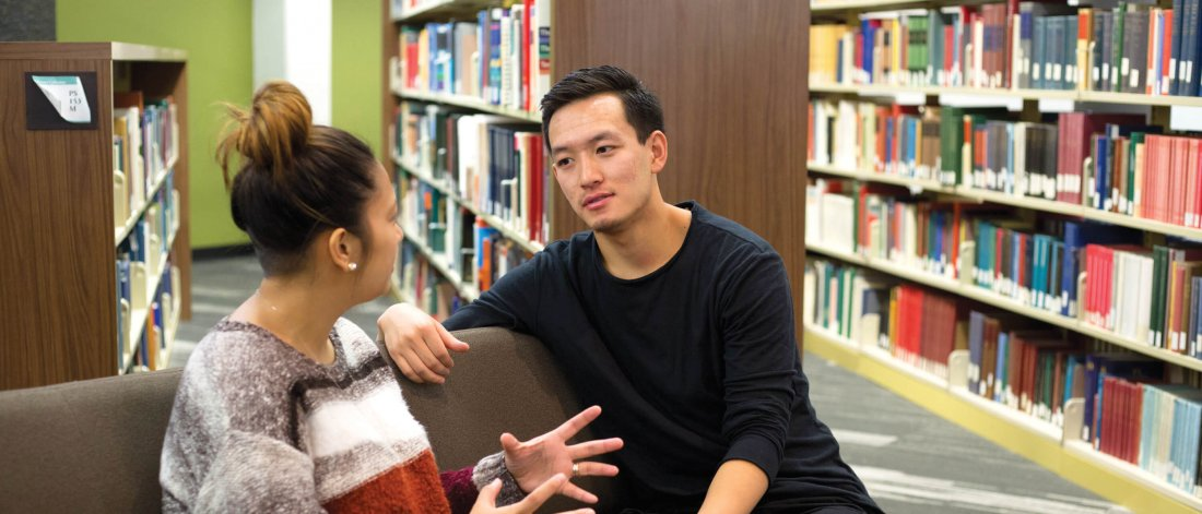 Two students sitting and talking together in a library.