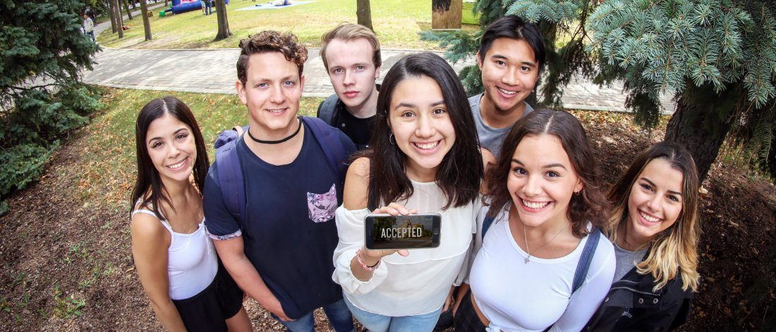 A group of recently graduated high school students stand together, one person holds a phone that has the word Accepted on the screen.
