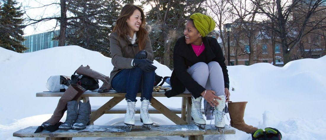Two young alumni lacing up ice skates on a bench