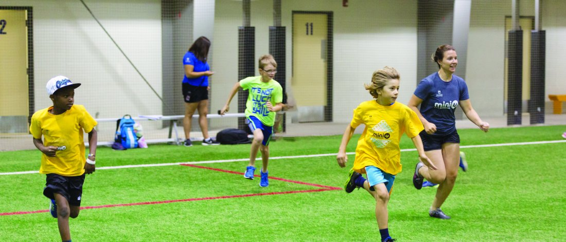 group of kids pictured in the fieldhouse, running and playing