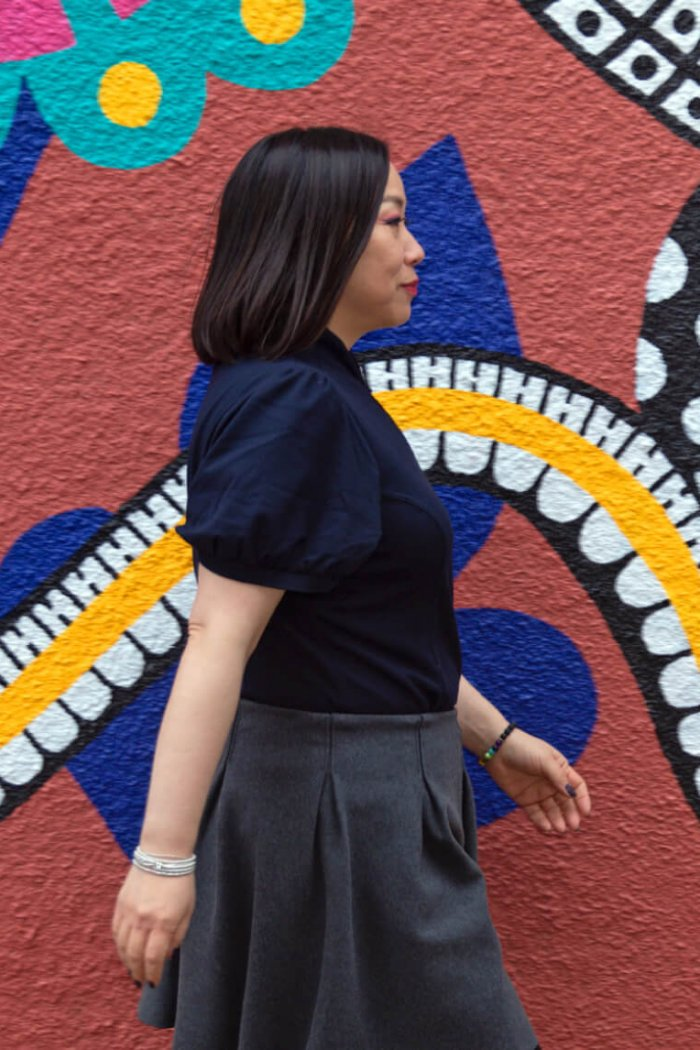 Hee-Jung Serenity Joo, associate professor of English, film theatre and media walking in front of a colourful wall mural.