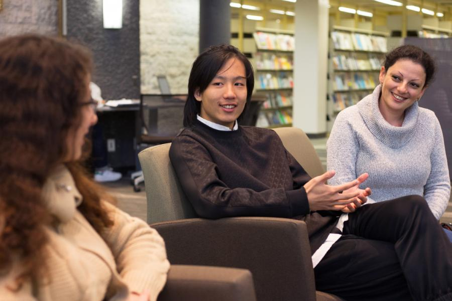 Three people sitting in a University of Manitoba Library having a conversation.