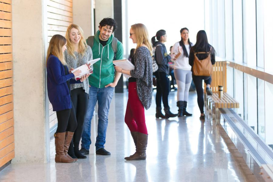 Undergraduate students chatting in the hall at the University of Manitoba.