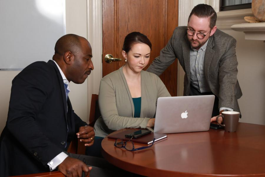 Three University of Manitoba staff sitting looking at laptop