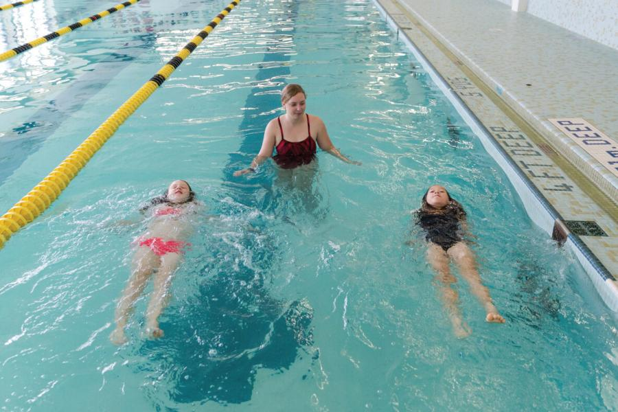 An instructor with two girls from the Mini U Aquatics Program