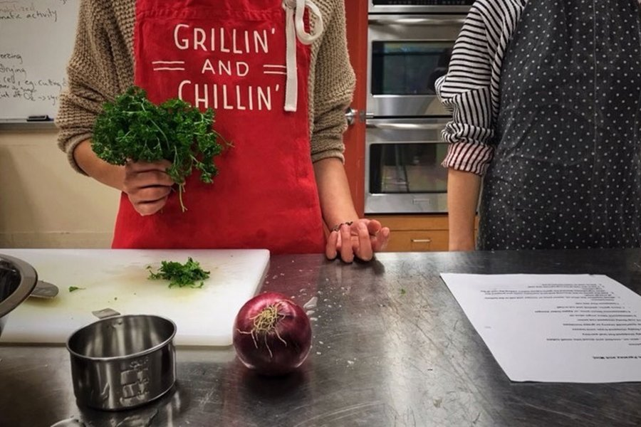 Chefs in a kitchen with an onion on the counter