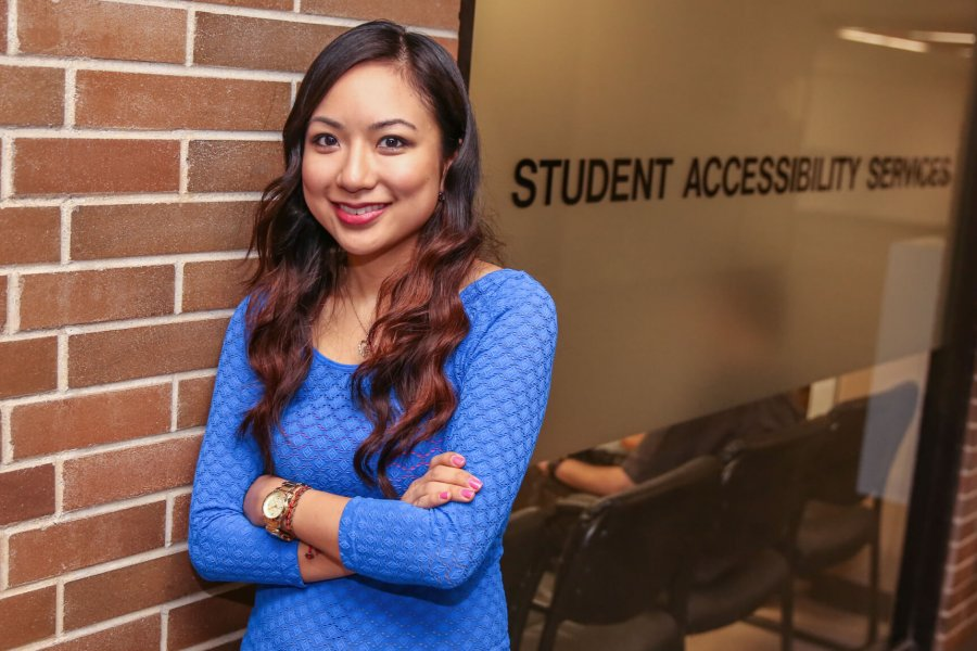 A smiling woman stands outside of the Student Accessibility Services office.
